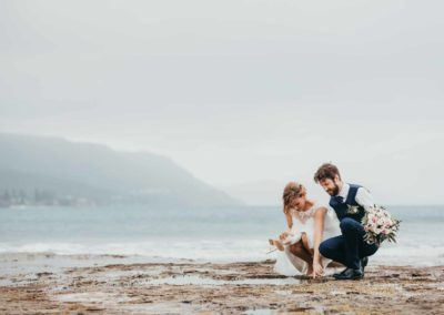 A couple explore the rock pools after their wedding