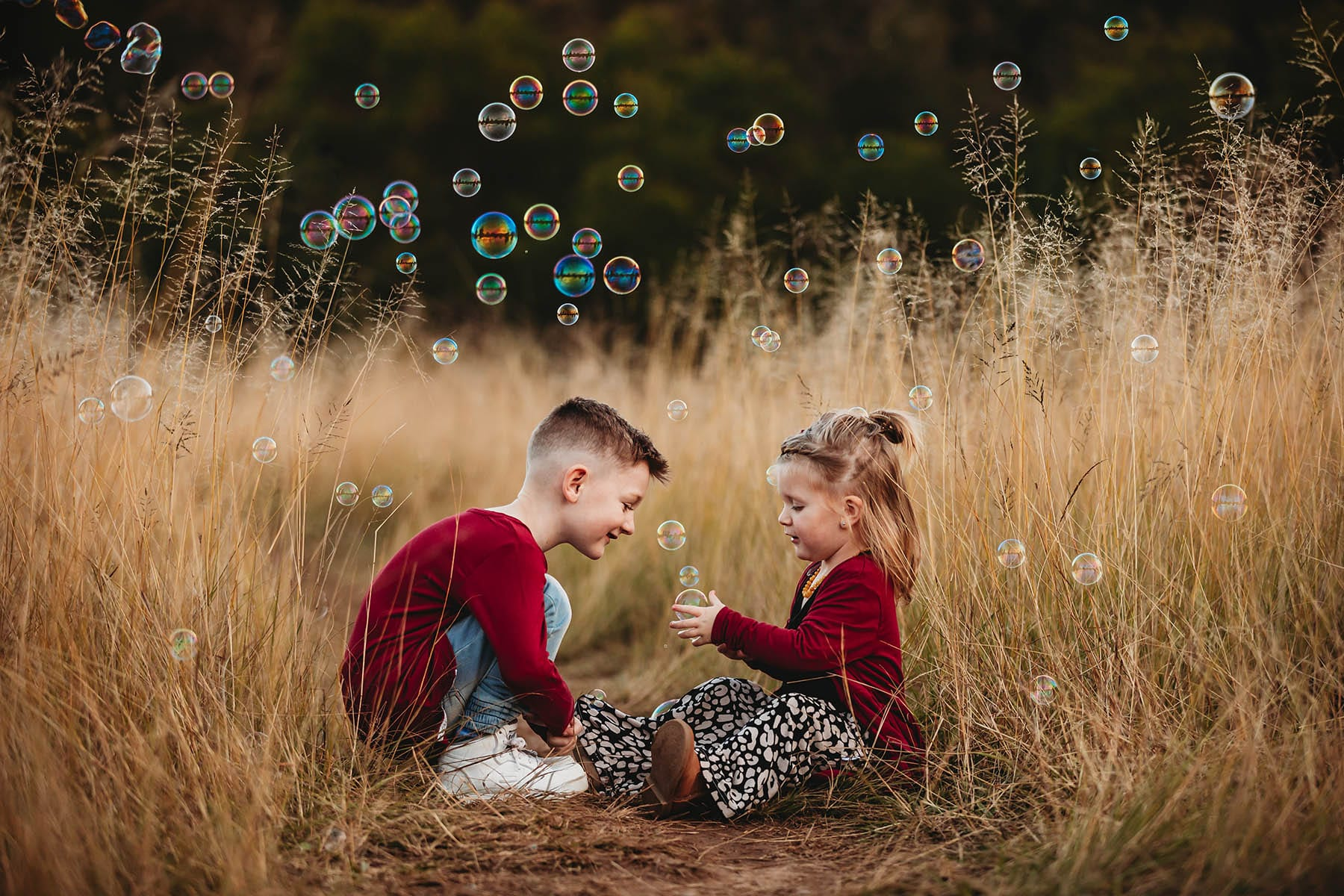 Siblings sitting on a dirt track in long grass playing with bubbles at sunset