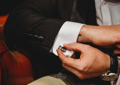 Detail photograph of a groom adjusting his cufflink