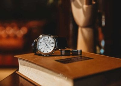 Detail photograph of a groom's wristwatch sitting on a book