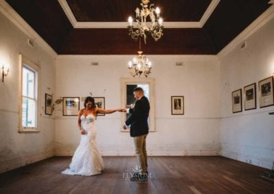 A groom twirls his bride as they practice their first dance in the Gledswood Homestead music room