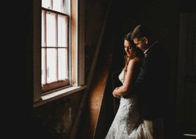 A groom cuddles his bride in a dimly lit room in front of a small window
