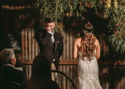 A groom is overcome with emotion as he sees his bride at their wedding ceremony