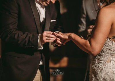 Detail photograph, a groom places the wedding ring on his brides finger