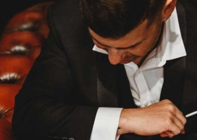 A groom admires his cufflink while preparing for the wedding