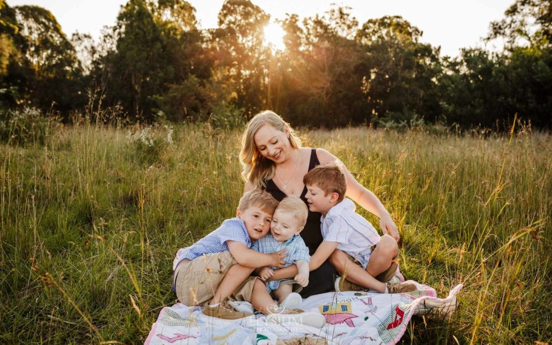 A family sit on a blanket in a grassy field, mother cuddles her 3 boys